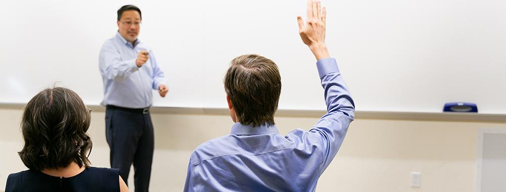man holding up his hand to ask a question of an instructor