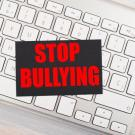 image of keyboard with text atop, reading Stop Bullying