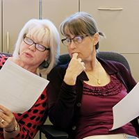 """two female colleagues reviewing a document"""