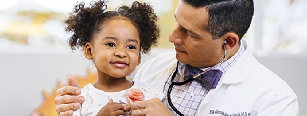 UC Davis Health physician talking to young child, arm wrapped around their shoulders, while using a stethoscope.
