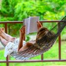 person in white dress reading on front porch, laying in hammock.